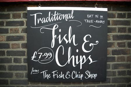 Fish and chips sign advertising the traditional English take away meal. Stock Photo