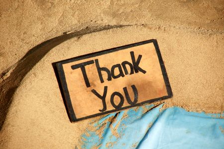 favour: Thank you sign on a sandy beach. Stock Photo
