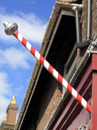 barber pole: Medieval Barbers Pole in Winchester England. The origin of the barber pole is associated with blood letting. In medieval times barbers performed surgery as well as tooth extraction. The red and white stripes represents bandages and blood Stock Photo