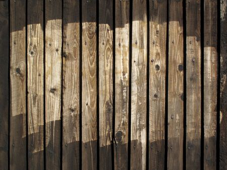 Old wooden half painted brown fence. photo