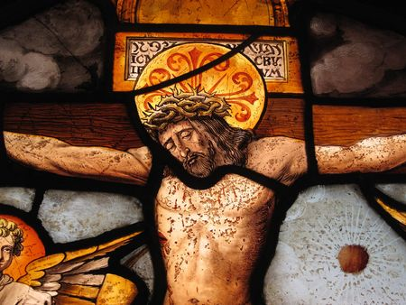 The crucifixion of Christ shown in an image on a medieval 16th century stained glass panel