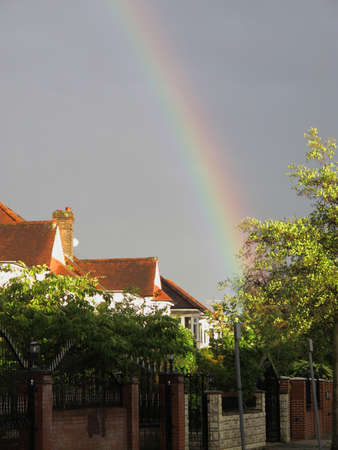 Rainbow with a dark overcast sky above suburban houses in London, England photo