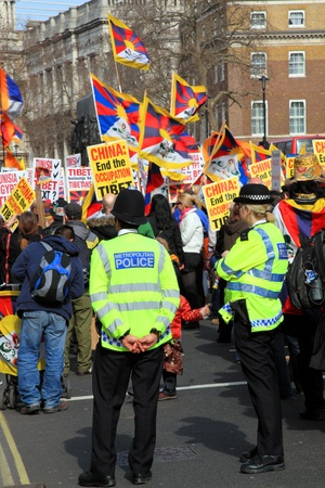 oppression: London, United Kingdom, Mar 12, 2011 : Tibetans and supporters, waving placards and flags of Tibet at a protest in Whitehall against the oppression of the China government against the people of Tibet Editorial