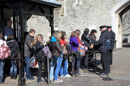 London, United Kingdom, Mar 19, 2011 : Security staff searching bags at the Tower London to prevent a terrorist attack, while tourist queue patiently