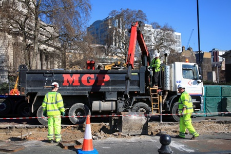 London, United Kingdom, Mar 19, 2011 : Roadworks in Tower Hill were manual workers are working as a team, using a mechanical digger to make essential road repairs in the City of London