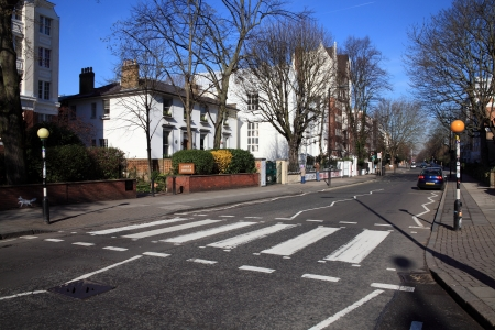 London, United Kingdom, Mar 19, 2011 : The  famous zebra  crossing in Abbey Road were the Beatles were photographed for the album Abbey Road, with Abbey Road studios in the background , tourists are photographing the recording studio Editorial