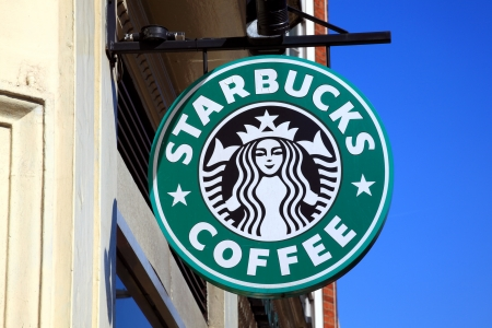 London, United Kingdom, Apr 9, 2011 : Starbucks green logo advertising sign hanging outside one of its coffee houses