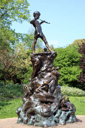 barrie: London, United Kingdom, Apr 17, 2011 : The Peter Pan statue in Kensington Gardens. The statue shows the boy who would never grow up, blowing his horn on a tree stump with mice, fairies and squirrels in a leafy glade Editorial