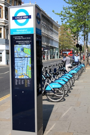 London, United Kingdom, Apr 17, 2011 : London Cycle Hire bikes at a docking station standing in a  row in Kensington Church Street with customers preparing to hire bikes, which display the  Barclays Bank logo who sponsor the scheme