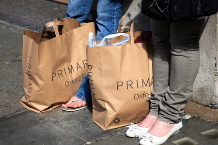 London, United Kingdom, May 8, 2011 : Shoppers resting in Oxford Street with Primark carrier bags at their feet
