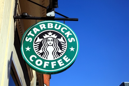 London, United Kingdom, Apr 9, 2011 : Starbucks green logo advertising sign hanging outside one of its coffee houses Editorial