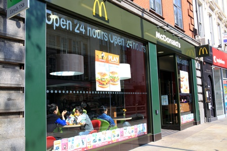 London, United Kingdom, Apr 17, 2011 : McDonald's fast food outlet in Kensington with its new green and yellow colours showing customers enjoying their food