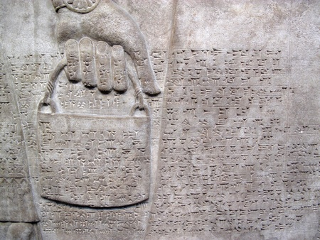 Assyrian relief 865-860 BC, showing cuniform script, of a royal helper carrying a bucket Editorial