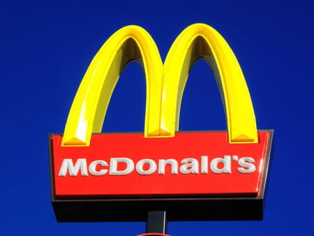 London, United Kingdom, Jun 2, 2011 : McDonald's yellow and red logo advertising sign placed on a pole with a clear blue sky Stock Photo - 10290497