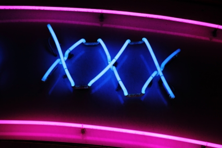 XXX neon sign advertising an adult licensed sex shop in a red light district Editorial