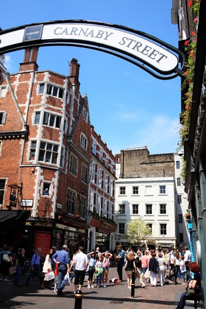 London, UK - Jun 4, 2011 : Tourists shopping  in Carnaby Street with a street busker playing a guitar
