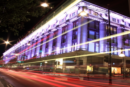 London, United Kingdom, Oct 6, 2011: Selfridges department store in Oxford Street at night, with blurred motion vehicle headlights and tail lights