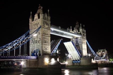 drawbridge: Tower Bridge at night with its drawbridge open on the River Thames in Tower Hamlets, London , England, UK Stock Photo