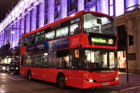 London, UK – Oct 6, 2011: No 10 London  red double decker bus at night, passing Selfridges Department Store in Oxford Street, on its journey across London to Warren Street