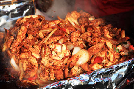 fajita: Fast food takeaway of cooked and simmering Mexican fajita filling simmering in a silver foil tray