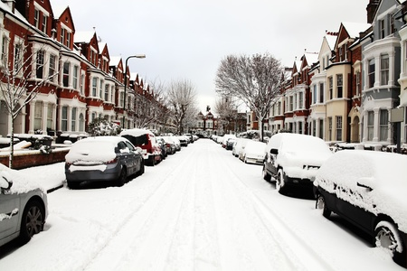 Snow cityscape of a terraced street in London England with slippery blizzard conditions showing cars covered with ice and a blanket of snow