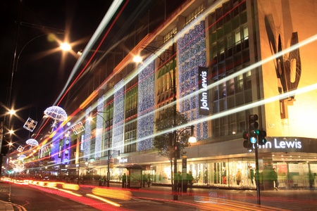 London, UK - November 10, 2011: The Christmas lights decorations outside John Lewis department store at night, in Oxford Street during the festive season. with blurred motion light trails. Stock Photo - 11305651