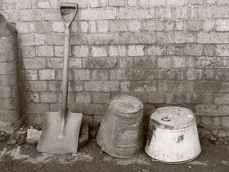 Black and white toned sepia retro photograph of old vintage buckets and a spade resting against an old Victorian wall Stock Photo - 11714262