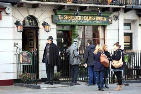 private investigator: London, UK - January 6, 2012: Tourist and a Policeman actor outside the Sherlock Holmes Museum at 221B Baker Street, the home of the famous fictitious Victorian private detective