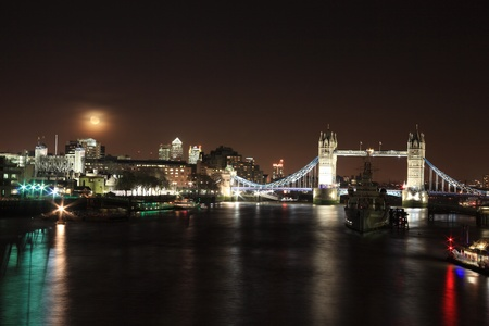 hms: Cityscape of the River Thames at night in London, England, UK showing  Tower Bridge, Tower of London, Canary Wharf, Docklands and HMS Belfast with the moon in the sky. Stock Photo