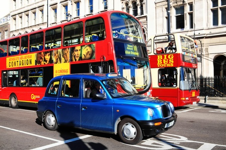 black cab: London, UK – October 15, 2011: Public transport in Whitehall, Westminster showing a London taxi, a double decker bus and Big Bus tour operator open top bus