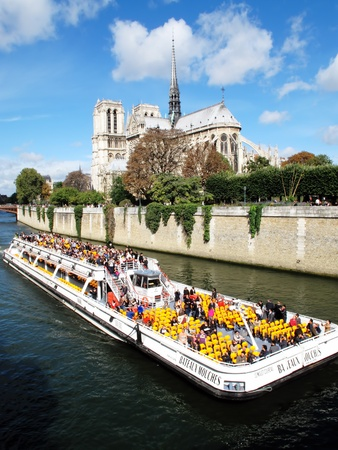 notre dame: Paris, France � September 18, 2011: Tourist enjoying a tour of the River Seine passing Notre Dame cathedral aboard a Bateaux Mouches boat