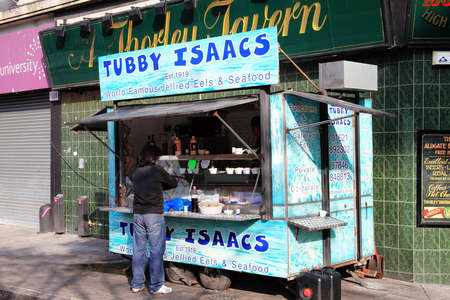 british food: London, UK - October 23, 2011: Tubby Isaacs seafood stall  in Goulston Street, Aldgate at Petticoat Lane Market, a customer is being served with his jellied eels order