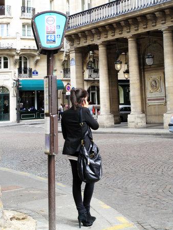 parada de autobus: Par�s, Francia, 18 de septiembre de 2011: Una mujer joven de pie en una parada de autob�s utilizando un tel�fono m�vil en la calle de Richelieu Editorial