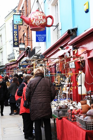 London, UK - February 19, 2012:  Customers looking at merchandise on market stalls in Portobello Road market