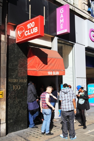 London, United Kingdom, April 1, 2012 : Visitors using there mobile phones and talking while waiting outside the 100 Club in Oxford Stree