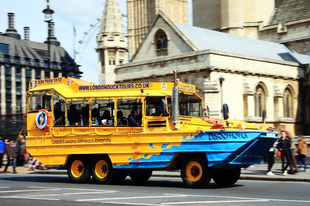 amphibious: London, UK - April 6, 2012:  A London Duck Tour amphibious DUCW vehicle full of tourists, passing the Houses of parliament on its way to the River Thames Editorial