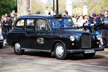 London Black taxi cab passing sightseeing tourists near the Buckingham Palace gate of Green Park