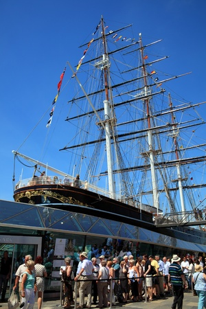queueing: London, UK - May 27, 2012: The Cutty Sark tea clipper ship in Greenwich, with visitors queueing to to see the now restored ship, which was damaged by fire