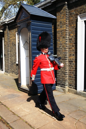 guard house: London, UK - April 14, 2012: Coldstream Guard marching near his sentry box in The Mall outside Clarence House