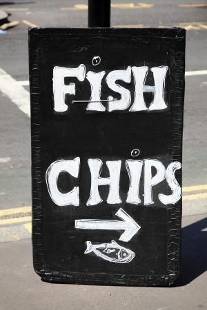 fish and chips: Peces del Reino Unido y los chips de la señal de publicidad tradicional Inglés llevar comida Foto de archivo