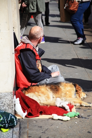 London, UK, April 11, 2012 : A homeless Big Issue vendor in Oxford Street resting on the pavement with his dog at his side