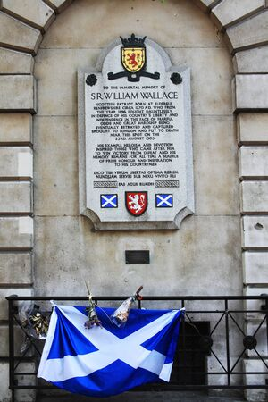 named person: London, United Kingdom, April 30, 2011 : A memorial plaque to Sir William Wallace (Braveheart) outside St Bartholomews Hospital in Smithfields, decorated with flowers and the Scottish flag, which have been left by visitors