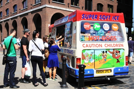 queueing: London, UK - July 22, 2012: Tourist buying ice cream cones and refreshments from an ice cream van outside Trinity Square opposite the Tower of London