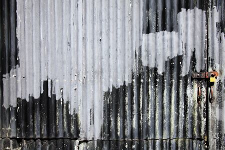 Distressed old corrugated iron fence with a door background photo