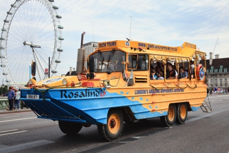 amphibious: London, UK - August 19, 2012:  A London Duck Tour amphibious DUCW vehicle full of tourists, passing over Westminster Bridge on its way to the River Thames
