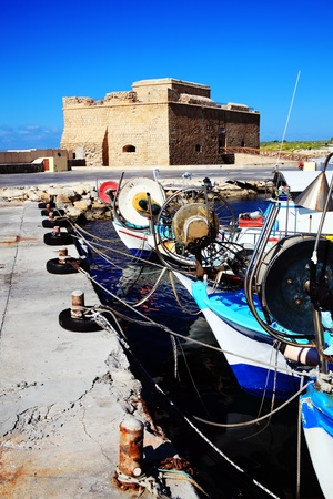 Paphos Castle, originally built as a Byzantine fort, which stands guarding the harbour in Paphos, Cyprus and now a museum, with fishing boats in the foreground