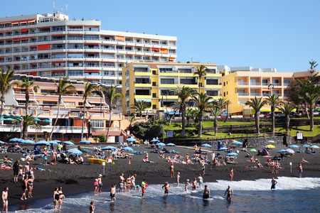 Tenerife, Canary Islands, Spain, March 24, 2014   Holidaymakers on vacation making the most of the winter sun on the volcanic black sand beach of Playa de la Arena tourist resort