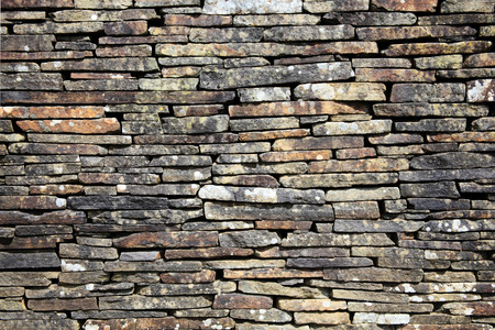 Dry stone wall stacked high to form a boundary photo