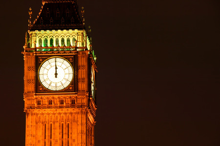after midnight: New Year Eve night  image at midnight of the illuminated clock face of Big Ben of the Houses Of Parliament in Westminster, London England, UK which was built on the site of the Royal Palace Of Westminster, in a Gothic style, after a fire in 1834