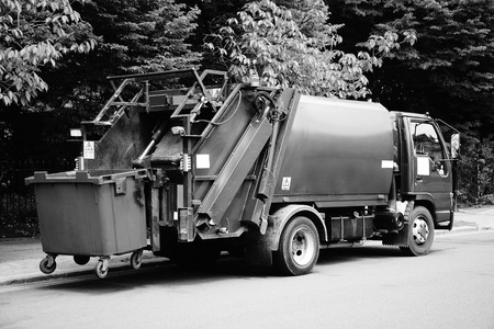 Black and white monochrome photograph picture of a Green garbage truck vehicle with an elevated blue wheelie bin at the rear, which is collecting dustbin rubbish for recycling